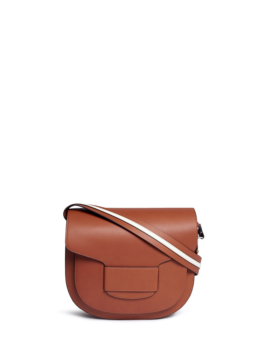 Modern Buckle leather saddle bag by Tory Burch